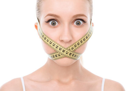 eyes wide: Portrait of a beautiful young blond fit girl wearing white bra looking shocked, eyes wide opened, measuring tape on her face isolated on a white background, close up