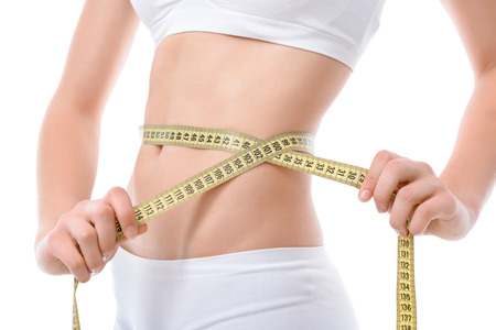 waistline: Close up photo of a fit girl wearing white bra and panties ,holding a measuring tape with her hands on waistline, isolated on a white background