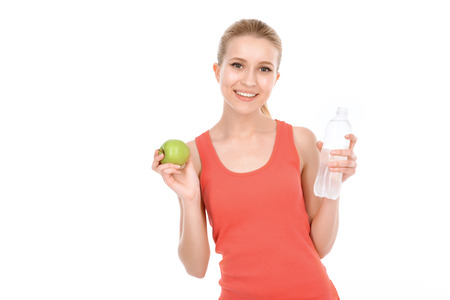 waist up: Portrait of a beautiful young blond fit girl wearing a red top holding an apple and a bottle of still water and smiling happily, isolated on a white background, waist up Stock Photo
