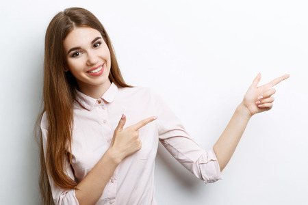 waist up: Portrait of a young beautiful girl with long brown hair wearing pink cotton blouse, standing waist up smiling and pointing with two hands to the left, on a white background