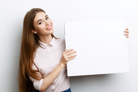 waist up: Portrait of a young beautiful girl with long brown hair wearing pink cotton blouse, standing waist up smiling and holding a copy space in her hands charming , on a white background