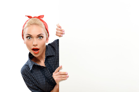Portrait of a beautiful blond pin up girl with ponytail and red bandana wearing a blue dotted dress looking surprised behind a copy space, isolated on white background