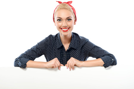 red bandana: Portrait of a beautiful blond pin up girl with ponytail and red bandana wearing a blue dotted dress sitting smiling showing teeth, isolated on white background