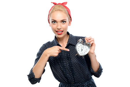 red bandana: Portrait of a beautiful blond pin up girl with ponytail and red bandana wearing a blue dotted dress smiling and pointing at a small heart-shaped clock in her hand, isolated on white background
