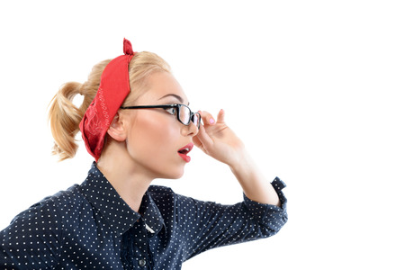 red bandana: Portrait of a beautiful blond pin up girl with ponytail and red bandana wearing a blue dotted dress touching her glasses looking very surprised, side view, isolated on white background