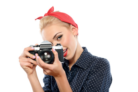 red bandana: Portrait of a beautiful blond pin up girl with ponytail and red bandana wearing a blue dotted dress holding vintage camera making a photo seductively, isolated on white background