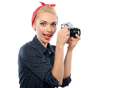 red bandana: Portrait of a beautiful blond pin up girl with ponytail and red bandana wearing a blue dotted dress holding vintage camera with a funny face, isolated on white background Stock Photo