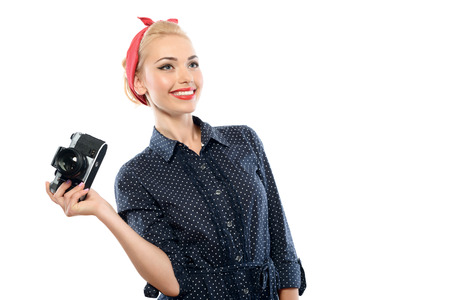 red bandana: Portrait of a beautiful blond pin up girl with ponytail and red bandana wearing a blue dotted dress holding vintage camera smiling looking aside, isolated on white background