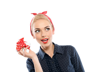 red bandana: Portrait of a beautiful blond pin up girl with red bandana wearing a blue dotted dress holding a small white present with red ribbon in her hand wondering what is inside, isolated on white background