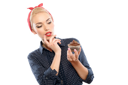 bandana girl: Portrait of a beautiful blond pin up girl with ponytail and red bandana wearing a blue dotted dress holding a chocolate cupcake wondering how many calories are in it, isolated on white background