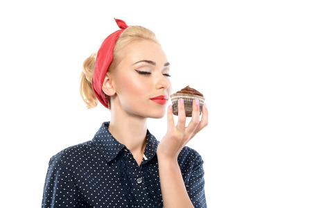 red bandana: Portrait of a beautiful blond pin up girl with ponytail and red bandana wearing a blue dotted dress holding a chocolate cupcake and smelling it smiling, isolated on white background Stock Photo