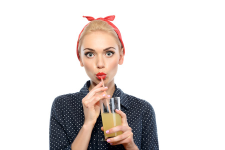 red bandana: Portrait of a beautiful blond pin up girl with ponytail and red bandana wearing a blue dotted dress holding a glass of juice and drinking it, isolated on white background
