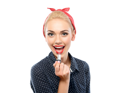 red bandana: Portrait of a beautiful blond pin up girl with ponytail and red bandana wearing a blue dotted dress painting her lips with red lipstick smiling, isolated on white background