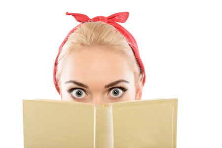 red bandana: Portrait of a beautiful blond pin up girl with ponytail and red bandana hiding behind a yellow book playing with her eyes wide opened, isolated on white background