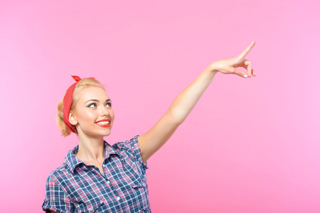 bandana girl: Portrait of a beautiful blond pin up girl with ponytail and red bandana wearing a blue checkered shirt pointing somewhere looking aside and smiling, isolated on pink background Stock Photo