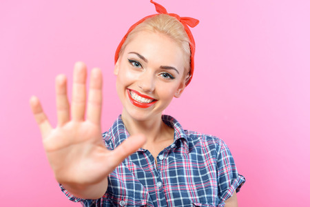 red bandana: Portrait of a beautiful blond pin up girl with ponytail and red bandana wearing a blue checkered shirt giving five and smiling, selective focus, isolated on pink background Stock Photo