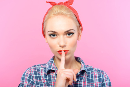 red bandana: Portrait of a beautiful blond pin up girl with ponytail and red bandana wearing a blue checkered shirt holding a finger near her mouth showing to be quiet, isolated on pink background Stock Photo