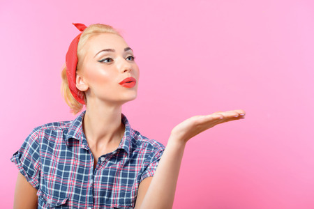 red bandana: Portrait of a beautiful blond pin up girl with ponytail and red bandana wearing a blue checkered shirt blowing a kiss, isolated on pink background Stock Photo