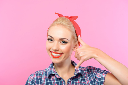 red bandana: Call me. Portrait of a beautiful blond pin up girl with ponytail and red bandana wearing a blue checkered shirt showing telephone with her hand, isolated on pink background