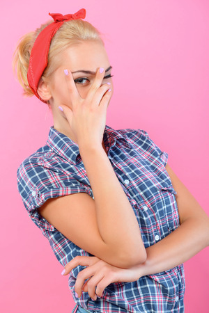bandana girl: Portrait of a beautiful blond pin up girl with ponytail and red bandana wearing a blue checkered shirt smiling and hiding behind her hand, isolated on pink background