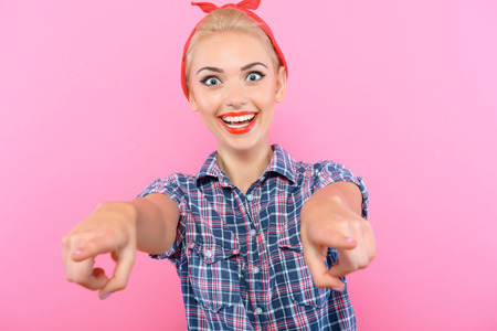 red bandana: Portrait of a beautiful blond pin up girl with ponytail and red bandana wearing a blue checkered shirt smiling and pointing at you selective focus, isolated on pink background