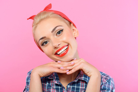 bandana girl: Portrait d'une belle blonde Pin Up Girl avec queue de cheval et bandana rouge v�tue d'une chemise � carreaux bleu souriant et �tayer sa t�te, isol� sur fond rose Banque d'images