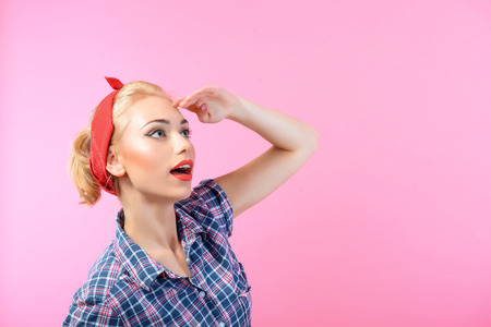 bandana girl: Portrait of a beautiful blond pin up girl with ponytail and red bandana wearing a blue checkered shirt looking somewhere aside holding hand above her head, isolated on pink background