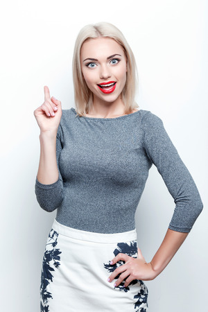 Having idea. Young pretty blond-haired woman standing on white isolated background and pointing upwards with her index finger photo