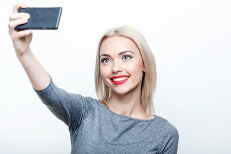 rubia: Hora de selfie. Sonriente joven de pelo rubio señora haciendo selfie sobre fondo blanco aislado