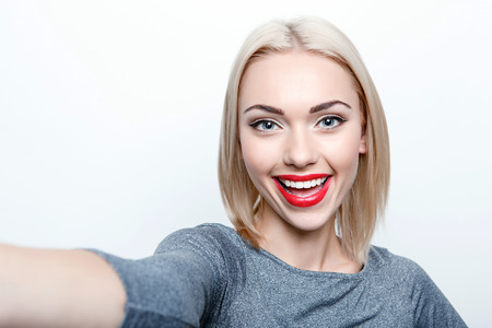 sexy blonde girl: Taking picture. Smiling cheerful blond-haired woman doing selfie on isolated white background