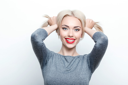 youthful: Looking playful. Portrait of youthful attractive woman touching her hair on isolated white background