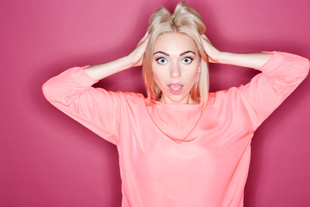 Oh my god. Portrait of young pretty woman touching her hair with great amazement on isolated pink background Stock Photo