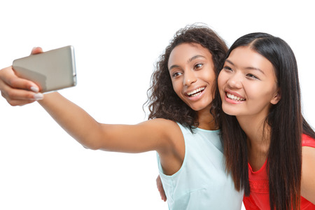vivacious: Great shot. Nice vivacious friends holding smart phone and looking on it while making selfie photos.