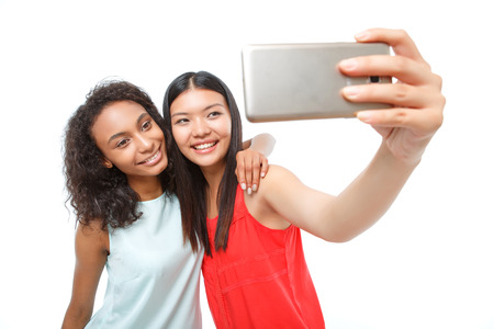 upbeat: Just to remember. Positive upbeat young ladies holding smart phone and smiling while making snaps. Stock Photo