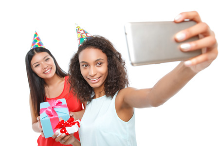 happy moment: Happy moment. Positive young girls making selfie pictures and smiling while holding presents in their hands.