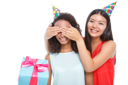 agreeable: Nice birthday. Agreeable young girl holding the present and smiling with the other girl keeping her eyes closed with palms.