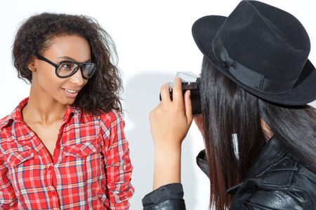 enjoyable: Enjoyable process. Bright positive girl wearing glasses and posing while her friend making photos.