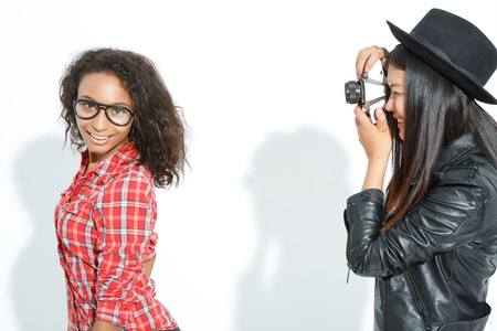 agreeable: Cheese. Agreeable young lady looking at the camera while posing with friend taking picture of her.