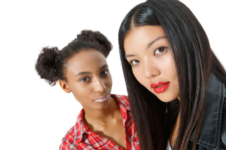 inscrutable: Inscrutable sight. Portrait of nice girls keeping mysterious glance at the camera and standing together isolated on white background.