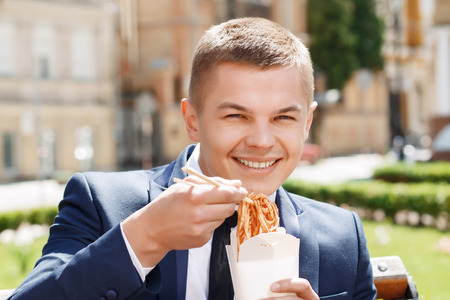 sensational: Happy food. Portrait of young smiling businessman eating Chinese noodle soup outside.
