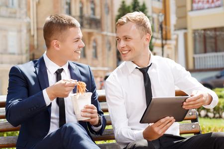 amigas conversando: Conversación amistosa. Hombre hermoso joven que muestra algo en la mesa a otra que comer fideos chinos. Foto de archivo