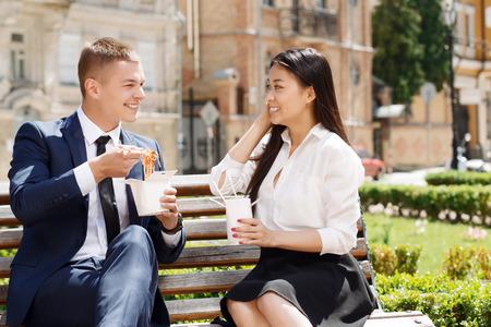 chinesisch essen: Schönes Paar. Mann und Frau sitzen auf Bank im Park, mit Gespräch und Essen chinesischen Nudeln.