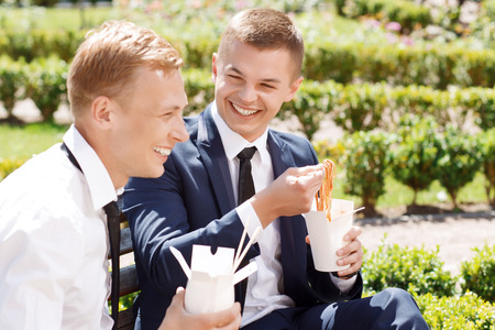 Lunch break. Pair of smiling handsome businessman  having conversation in park and eating Chinese noodles.