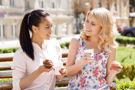 sensational: Funny conversation. Two young smiling girlfriends sitting in park and holding cupcakes with coffee.