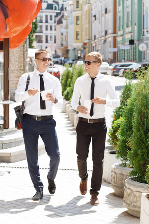 eating up: Having walk. Two youthful men walking through street and holding Chinese fast food.