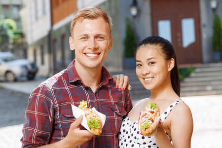 hotdog sandwiches: Going to eat. Young Caucasian man and Asian woman standing on street and holding hotdogs