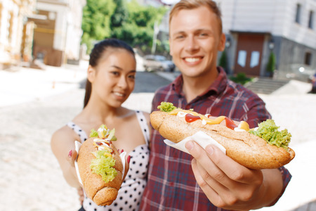 hotdog sandwiches: Look at it. Handsome man and pretty young woman standing on street and showing their delicious hotdogs.