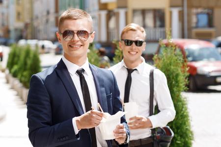 comida rapida: Par feliz. Retrato de hombres guapos jóvenes de pie en la calle con la comida rápida china.