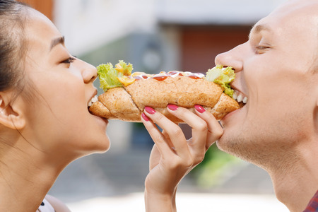 hotdog sandwiches: Sharing food. Young handsome man and pretty woman standing and biting off same hotdog.
