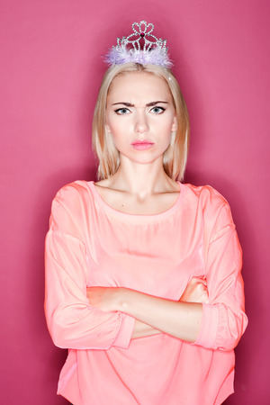 resentful: Hurt prices. Pretty resentful woman with crown standing on isolated pink background with very offended look. Stock Photo